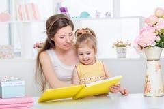 Мама и дочь читая совместно Стоковая Фотография