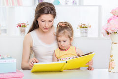 Мама и дочь читая совместно Стоковая Фотография RF