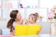Мама и дочь читая совместно Стоковое Изображение