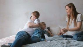 Мама и папа играют при двойные малыши мальчиков лежа на кровати Выходной день семьи видеоматериал