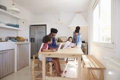 Мама и папа помогают их детям с домашней работой на кухонном столе Стоковое фото RF