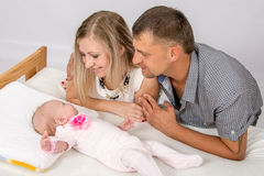 Мама и папа при улыбка, смотря ее двухмесячного младенца стоковые изображения