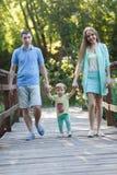Мама и папа с маленькой дочерью идут через мост стоковая фотография rf