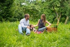 Мама и папа с ребёнком на пикнике Стоковые Изображения