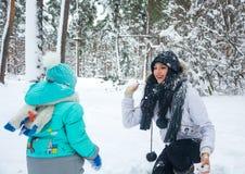 Мама и ребенок играют снежные комья в лесе зимы Стоковые Изображения RF