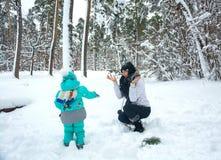 Мама и ребенок играют снежные комья в лесе зимы Стоковые Фото