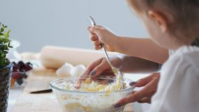 Мама и ребенок кладут сахар и смешивать тесто для блинчиков стоковые фотографии rf