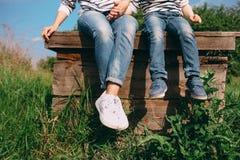 Мама и ребенок сидят на краю старого деревянного колодца стоковое изображение