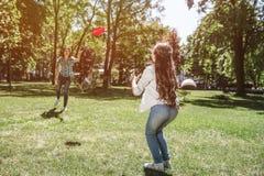 Мама и ребенок стоят перед ech другим и играют с frisbee Женщина бросает ее к девушке Ребенок стоковая фотография