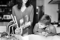 Мама и сын варя совместно жизнерадостную концепцию стоковое фото