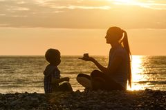 Мама и сын играют на пляже на заходе солнца Стоковое Изображение