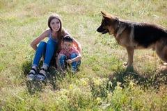 Мама и сын играя с тренировкой овчарки собаки стоковое фото rf