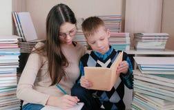 Мама и сын прочитали книгу совместно Мама в стеклах пишет что-то в тетради Стоковые Изображения RF