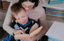 Мама и сын прочитали книгу совместно Мама в стеклах Стоковые Изображения RF
