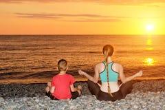 Мама и сын размышляют на пляже в положении лотоса Взгляд от задней части, заход солнца Стоковые Изображения RF