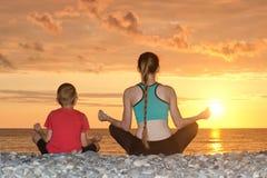 Мама и сын размышляют на пляже в положении лотоса Взгляд от задней части, заход солнца Стоковое фото RF