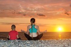 Мама и сын размышляют на пляже в положении лотоса Взгляд от задней части, заход солнца Стоковые Фотографии RF