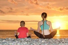 Мама и сын размышляют на пляже в положении лотоса Взгляд от задней части, заход солнца Стоковые Изображения