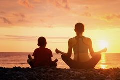 Мама и сын размышляют на пляже в положении лотоса Взгляд от t Стоковое Изображение