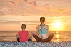Мама и сын размышляют на пляже в положении лотоса Взгляд от t Стоковое Фото