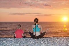 Мама и сын размышляют на пляже в положении лотоса Взгляд от t Стоковые Фото
