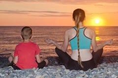 Мама и сын размышляют на пляже в положении лотоса Взгляд от t Стоковые Изображения RF