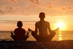 Мама и сын размышляют на пляже в положении лотоса Силуэты Стоковые Изображения