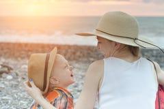 Мама и сын смеются над пока сидящ на пляже Стоковые Изображения RF