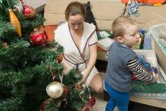 Мама и сын украшают рождественскую елку Стоковые Фотографии RF