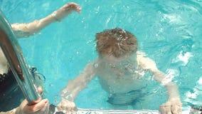 Мама конца-вверх счастливая учит, что ее сын плавает в бассейне r видеоматериал