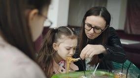 Мама кормит более молодую дочь с вилкой в кафе Обед семьи в кафе сток-видео