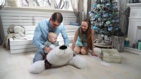 Мама кладет малого сына на плюшевый медвежонка акции видеоматериалы