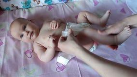 Мама кладет пеленку на младенца сток-видео