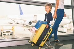 Мама носит ваш багаж с счастливым младенцем на крупный аэропорт Стоковое Изображение RF
