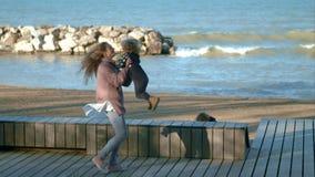 Мама обнимает ее сына и поворачивает дальше предпосылку моря сток-видео