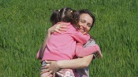 Мама обнимает детей в природе Женщина с маленькими девочками в парке на зеленой траве Семья обнимая на лужайке сток-видео