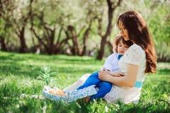 мама обнимает унылого сына малыша внешнего на прогулке любить семьи счастливый Стоковые Изображения