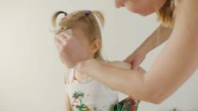 Мама освобождает сторону ее маленькой дочери, которая, во время встречи чертежа, была пакостна с красками видеоматериал