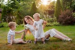 Мама, остатки 2 детей на природе Соперничество между детями Братья, материнство стоковые фото
