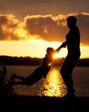 Мама отбрасывает сына в заходе солнца Стоковое Изображение RF