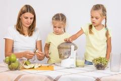 Мама отрезала сок груши, дети бросает их в juicer Стоковые Фотографии RF