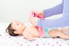 Мама одевая ее маленького младенца Стоковые Изображения