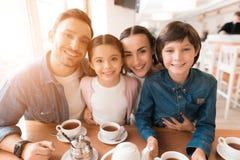 Мама, папа, дочь и сын представляя совместно на камере в кафе стоковые изображения rf