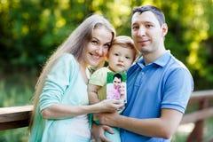 Мама, папа и маленькая девочка держа фото их жизней стоковое изображение