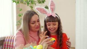 Мама поворачивает яйцо цыпленка желтое, и дочь рисует на голубых точках с вашими пальцами на держателе девушки с ушами кролика сток-видео
