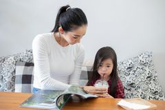 Мама поднимает стекло холодного молока, дочери выпивая и уча, что ее дочь прочитала книгу стоковое фото