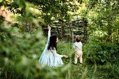 Мама показывает меньшему сыну птицу в дереве стоковое изображение rf