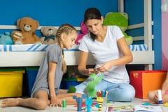 Мама помогает дочери отрезать вне диаграммы от покрашенной бумаги стоковые изображения rf