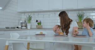 Мама помогает ее маленькому сыну съесть бургер в кухне видеоматериал