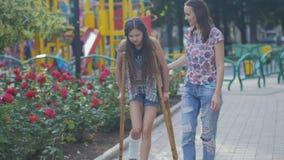 Мама помогает моей дочери с сломанной ногой на костылях идти вдоль улицы сток-видео